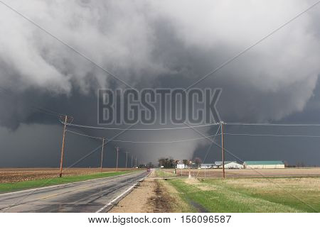 A huge, wedge shaped tornado crosses the highway just over a mile away from the photographer.