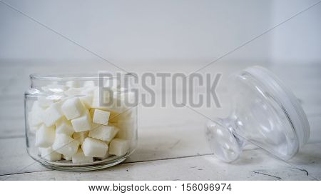 White sugar lumps in a glass jar on the wooden table painted in white color lies next the cover close up