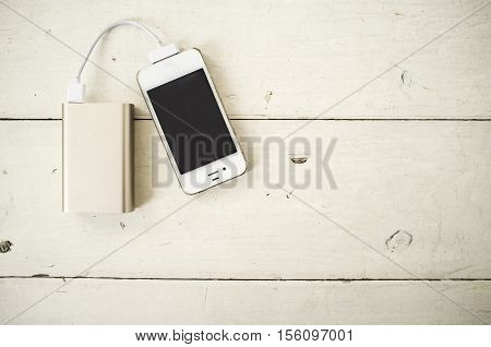 Smartphone is charged from the portable charging device for shabby the wooden table painted in white color