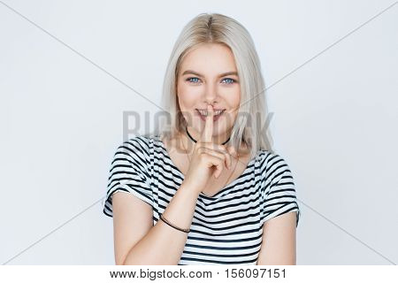 cute young woman with long blond dyed hair holding her finger on her mouth as she was keeping a secret isolated on white background