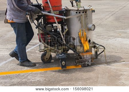 Man painting the yellow line on the concrete floor at car park