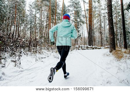woman runner of race leader is running a winter marathon on a snowy forest