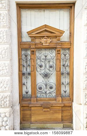 Massive wooden door on a white marble facade