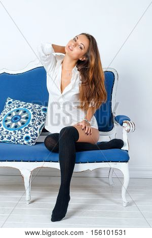 Sexy young woman in a man's shirt and leg warmers sitting on blue couch in white interior