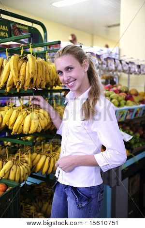Woman shopping for fruits in the supermarket buying bananas