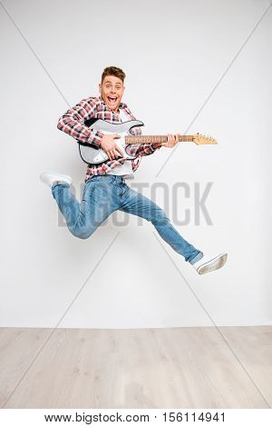 Portrait Of Crazy Energetic Man Jumping With Electric Guitar
