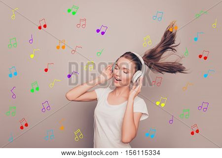 Portrait Of Happy Smiling Girl Listening Music In Headphones Over Background Of Notes
