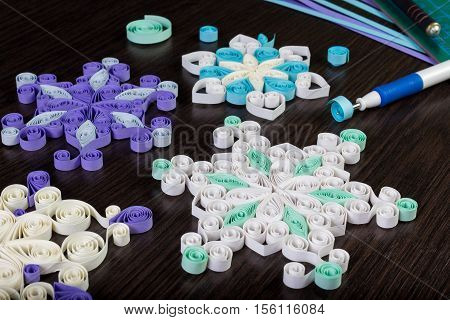 Handmade paper snowflakes with tools for quilling on dark wooden background. Preparation for Christmas.