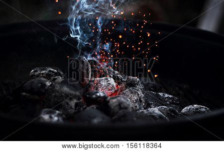 Charcoal that is smoking and burning on a grill