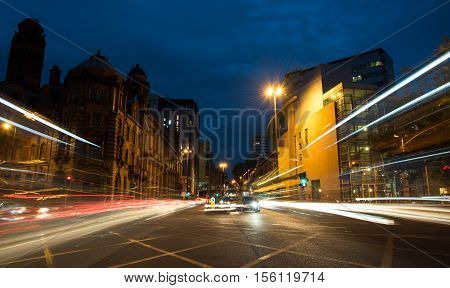 Light trails of cars and buses moving with speed at Piccadilly avenue near the main train station in the city of Manchester in England