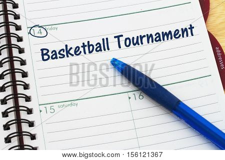 Your basketball tournament schedule a day planner with blue pen with text Basketball Tournament