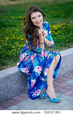 beautiful smiling woman in a blue dress sitting on the kerb in the Park.
