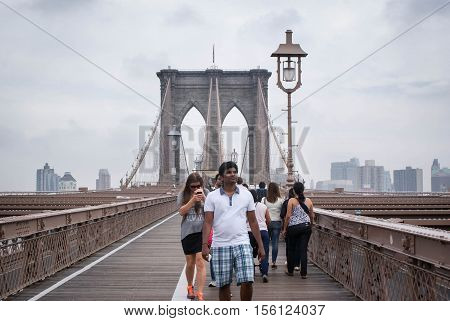 New York USA - September 22 2014: Tourists stroll the famous Brooklyn bridge in New York USA
