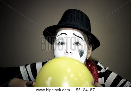 Girl with a yellow balloon in the form of mime actor