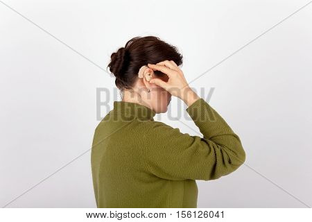 The Woman linserting her  brown hearing aid