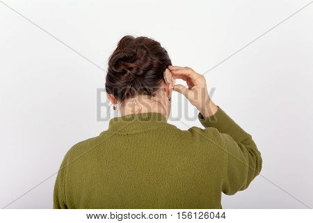 The Woman putting on a hearing aid