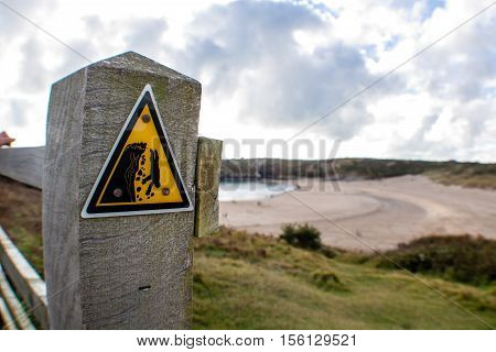 Warning sign for steep cliffs on a coastal path