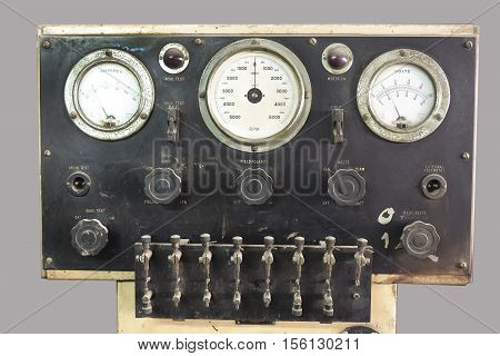 Front close up view on old control panel with adjustable valves dials and trio of gauges