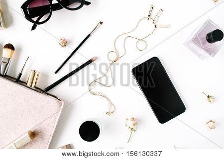 Flat lay top view office table desk frame. feminine desk workspace with clutch cosmetics phone sunglasses lipstick rose buds on white background.