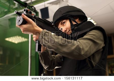 Woman in vest shot at the shooting range with a rifle