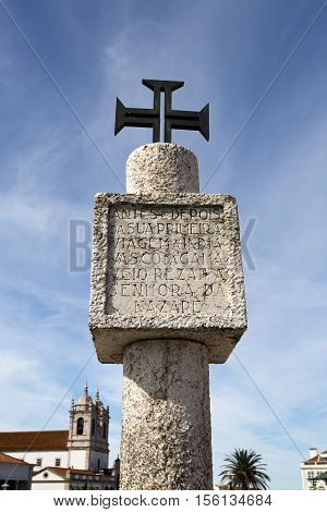 NAZARE, PORTUGAL - September 13, 2016: Limestone memory pillar with inscription and Order of Christ Cross located on the hilltop O Sitio overlooking Nazare Portugal. Translation: Where Vasco da Gama prayed before and after his voyage to India