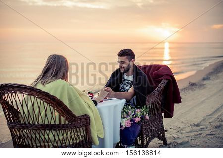 Pair and table on seacoast for a romantic meeting