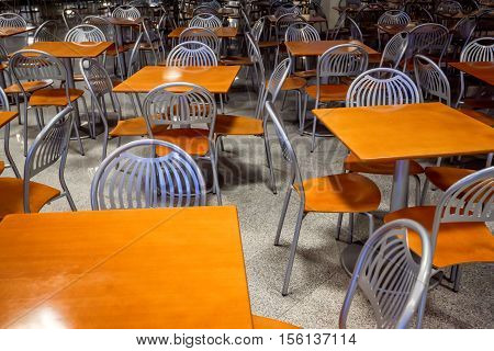 Silver shiny steel chairs and wooden tables in indoor industrial and modern style canteen - empty with nobody using the area