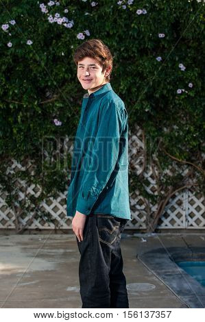 Handsome Latino teen smiling while turned at the waist in 3/4 pose.