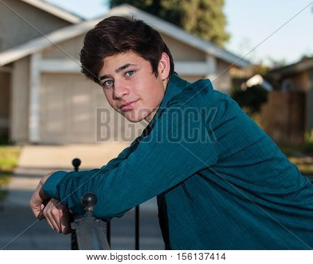 Handsome Latino teen leaning on handrail looking to left.