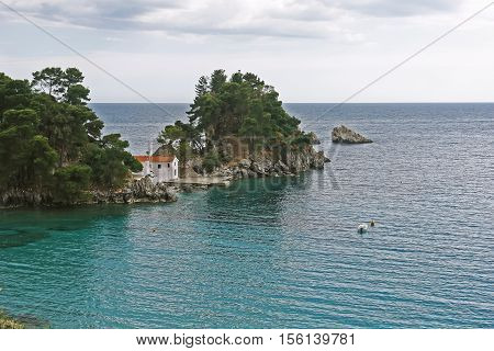 Parga GREECE May 09 2013: Landscape with church and boat in bay of Parga town on the coast of Ionian sea Greece.