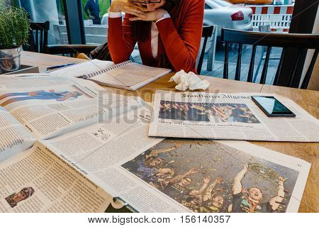 FRANKFURT, GERMANY - NOV 10 2016: Woman reading in cafe Frankfurter Allgemeine Zeitung newspaper with Donald Trump elected as President as the 45th President of United States of America