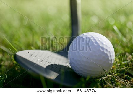 Lofted wedge resting behind a golf ball