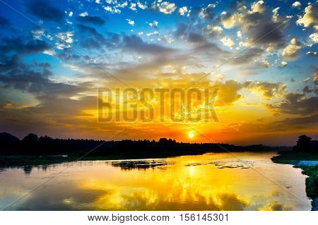 Beautiful lake landscape with vivid sunrise on the cloudy sky. River landscape. Beautiful summer landscape with golden sunset.