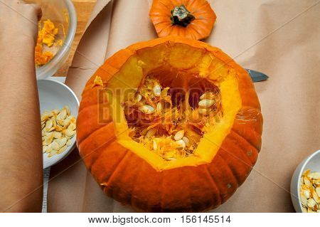 Looking into the top of a cut open pumpkin revealing the guts and seeds. The hand of a person is at the side separating the seeds from the strings.
