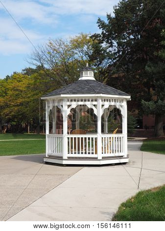 white gazebo by a cement sidewalk and trees