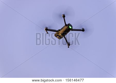 Close up of small modern drone taking photo while hovering against blue sky poster