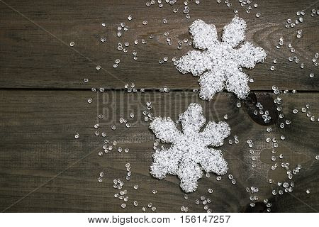Christmas decorations. White transparent snowflakes on a dark wooden background. Place for text. view from above