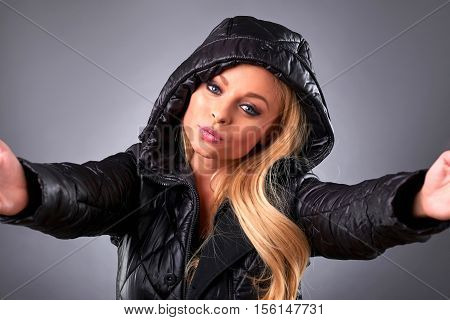 A beautiful young woman standing in a winter jacket and taking a selfie