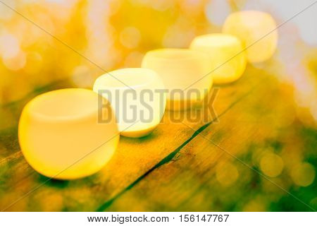 Group of aromatic candles light with bokeh on wooden table
