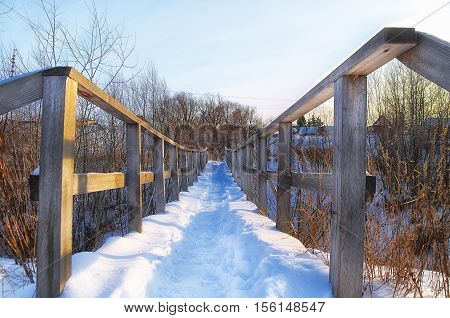 pedestrian bridge in the village covered with snow