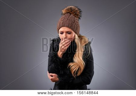 A beautiful young woman standing in an elegant black sweater and a brown hat and coughing