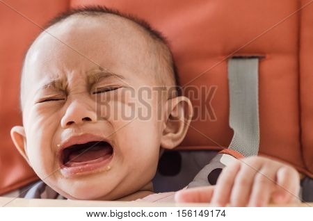 Asian baby girl sitting in highchair and crying refuses to eat food