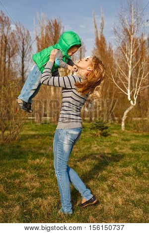 Mom tosses up her son in the autumn park. Family time. Happiness of childhood and motherhood. Outdoor Activities.