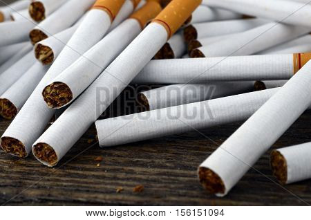 An image of multiple cigarettes pilled loosely on a table top.