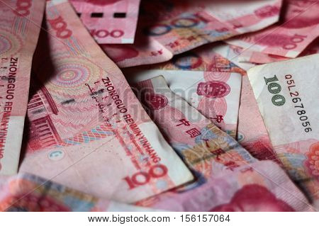 Full frame close-up of a pile of Chinese 100 yuan banknotes. Horizontal 3:2 format.