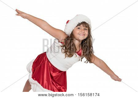 Cute smiling little girl in Santa Claus costume is leaning forward in front of the camera with her arms outstretched. All is isolated on the white background.