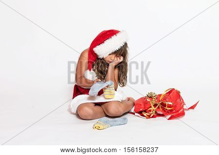 Sad little girl in Santa Claus costume with her hand supporting her chin is holding inappropriate gift (socks).