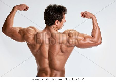 Athlete muscular bodybuilder showing back in studio on light grey background