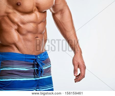 Athlete muscular bodybuilder part with copy space in studio on light grey background