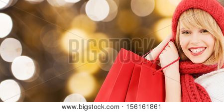people, holidays, winter, christmas and sale concept - young happy woman or teenage girl in red woolen knitted hat and scarf holding shopping bags over lights background